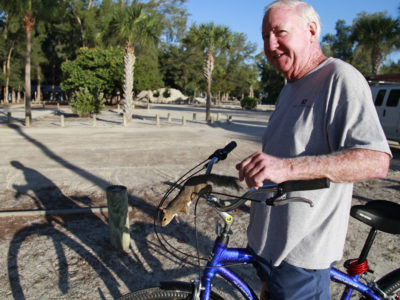 Bradenton Beach resident Paul Curtis is surprised by a friendly squirrel as he pauses on his morning bicycle ride on an Anna Maria Island bike trail that is accessible from the Bradenton Beach Scenic Highway. (Bradenton Beach Scenic Highway on Anna Maria Island is a waterfront highway corridor that offers nature, scenery, and pedestrian and bike-friendly paths. At 2.8 miles long, it offers panoramic views of the Gulf of Mexico and Sarasota Bay along Highway 789. It also includes access to Leffis Key, an island preserve with trails and plenty of wildlife and bird viewing.) (Bradenton Beach Scenic Highway) Photo made on 11/30/15 Photo by Lara Cerri