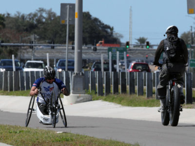 Tampa, Florida. 2/17/2016. A man navigates his custom wheelchair heading east from the Clearwater side of the scenic trail. Passing him going in the other direction is a security officer. Photos of the Courtney Campbell Scenic Highway and areas along it. Photo by Bill Serne