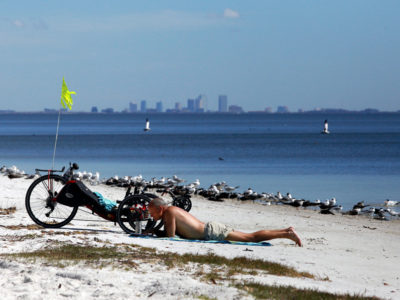 Tampa, Florida. 2/17/2016. With the Tampa skyline in the distance a beachgoer enjoys the west end sandy area of the highway and trail. Photos of the Courtney Campbell Scenic Highway and areas along it. Photo by Bill Serne