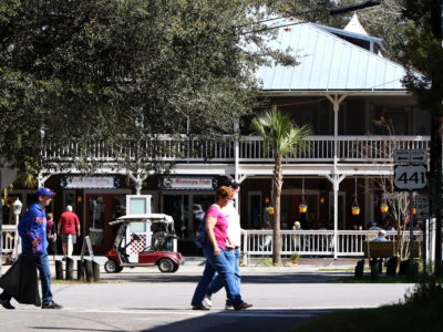 People walk past the Floirda Cafe which is on the Old Florida Heritage Highway in downtown Micanopy.   Photo by: Brad McClenny