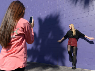 Mariana Risco takes a cell phone photograph of Kelsey Gallagher with Seaside, Florida's famous wall along Scenic Highway 30-A. The wall is a favorite spot for photographers and vacationers alike.