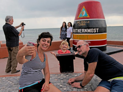 Overseas Highway- Bea and Olivier Louette of Belgium shoot a selfie with their 4 year old daughter Matilda at the Southernmost point of the United States where the Overseas Highway ends in Key West.