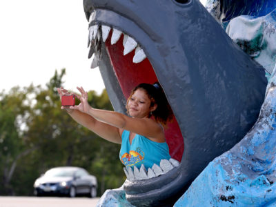 Overseas Highway- Brittany Holleran shoots her own photograph inside a photogenic shark's mouth along the scenic Overseas Highway in Big Coppitt Key in the lower Florida Keys.