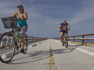 Overseas Highway- A couple rides their bikes along the old Seven Mile Bridge just south of Marathon in the Florida Keys.