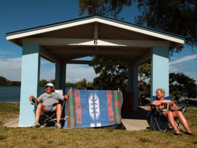 Bradenton Florida. 2/22/2016. At the Palma Sola Causeway Park, Bob and Tammy Bennington enjoy a sunny afternoon in and around one of the shelters. Their two dogs are behind the colorful blanket. They are from Cuyahoga Falls, Ohio. On the ground photos of the Palma Sola Scenic Highway and areas along it. Photo by Bill Serne