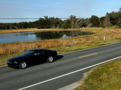 A car passes a lake along the Scenic Sumter Heritage Byway near Sumterville, Fla.