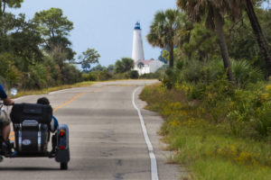 A motorcycle and sidecar travel to the St. Marks Lighthouse via a road inside the National WIldlife Refuge that surrounds it.. COLIN HACKLEY PHOTO