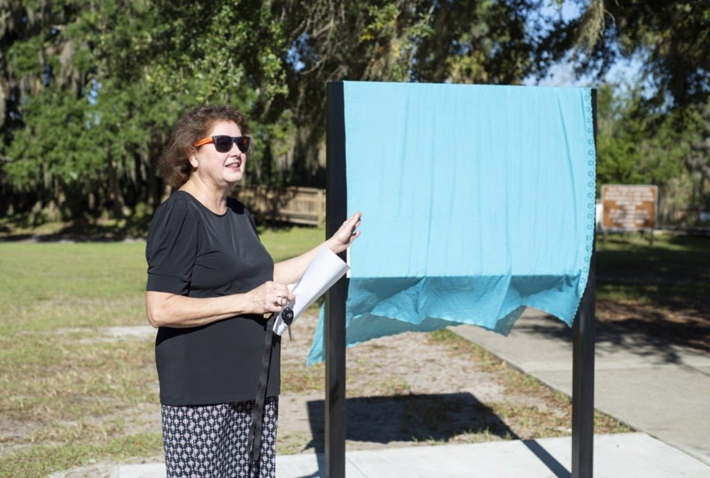 Cindy Sullivan, Chair of River of Lakes Heritage Corridor, wears her Florida Scenic Highways Program shades as she prepares for the unveiling.